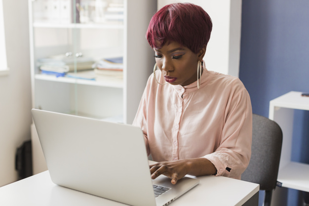 femme-noire-aide-ordinateur-portable-au-bureau_23-2147808047