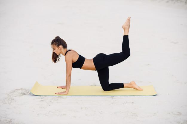 yoga-sport-fitness-concept-mode-vie-sain-yoga-girl-sportive-plage-pratique-coups-pied-arriere-s-appuyant-ses-mains_141188-2841